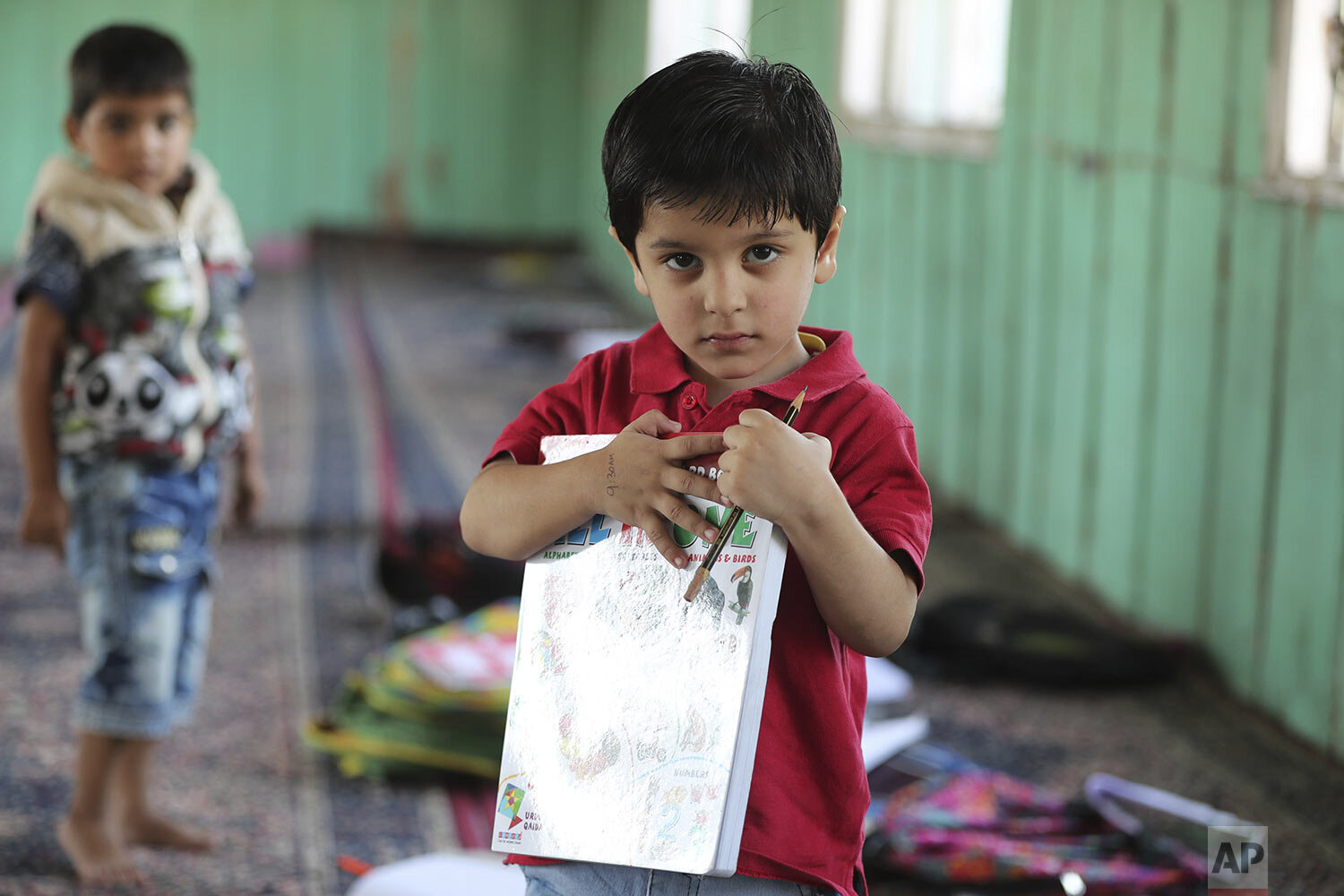 Children study inside a local mosque during a free classe by locals in Srinagar, Indian controlled Kashmir, Thursday, Sept. 19, 2019. (AP Photo/Mukhtar Khan)