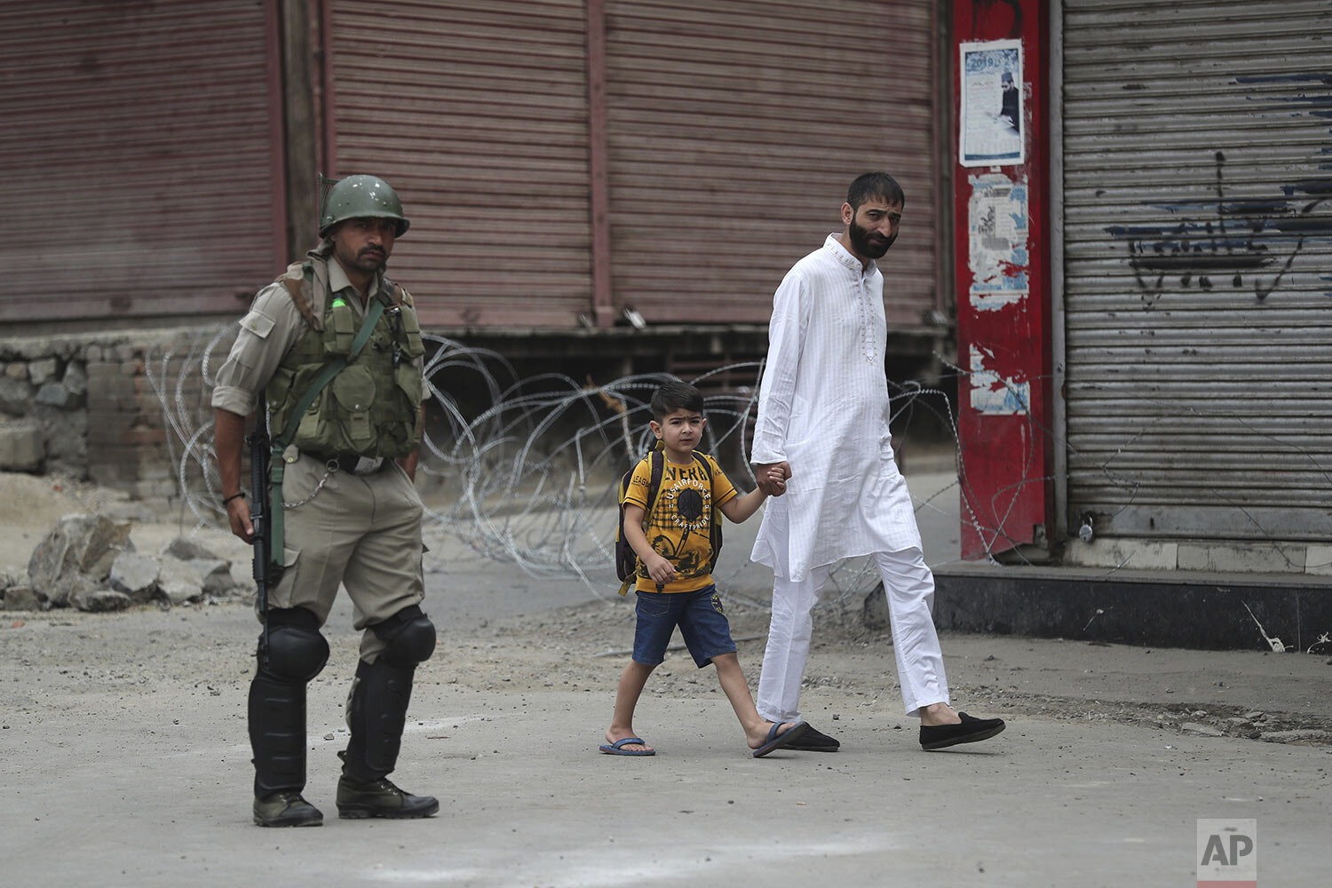 A man walks with a child past an Indian paramilitary soldier standing guard during restrictions ahead of Friday prayers in Srinagar, Indian controlled Kashmir, Friday, Aug. 30, 2019. (AP Photo/Mukhtar Khan)