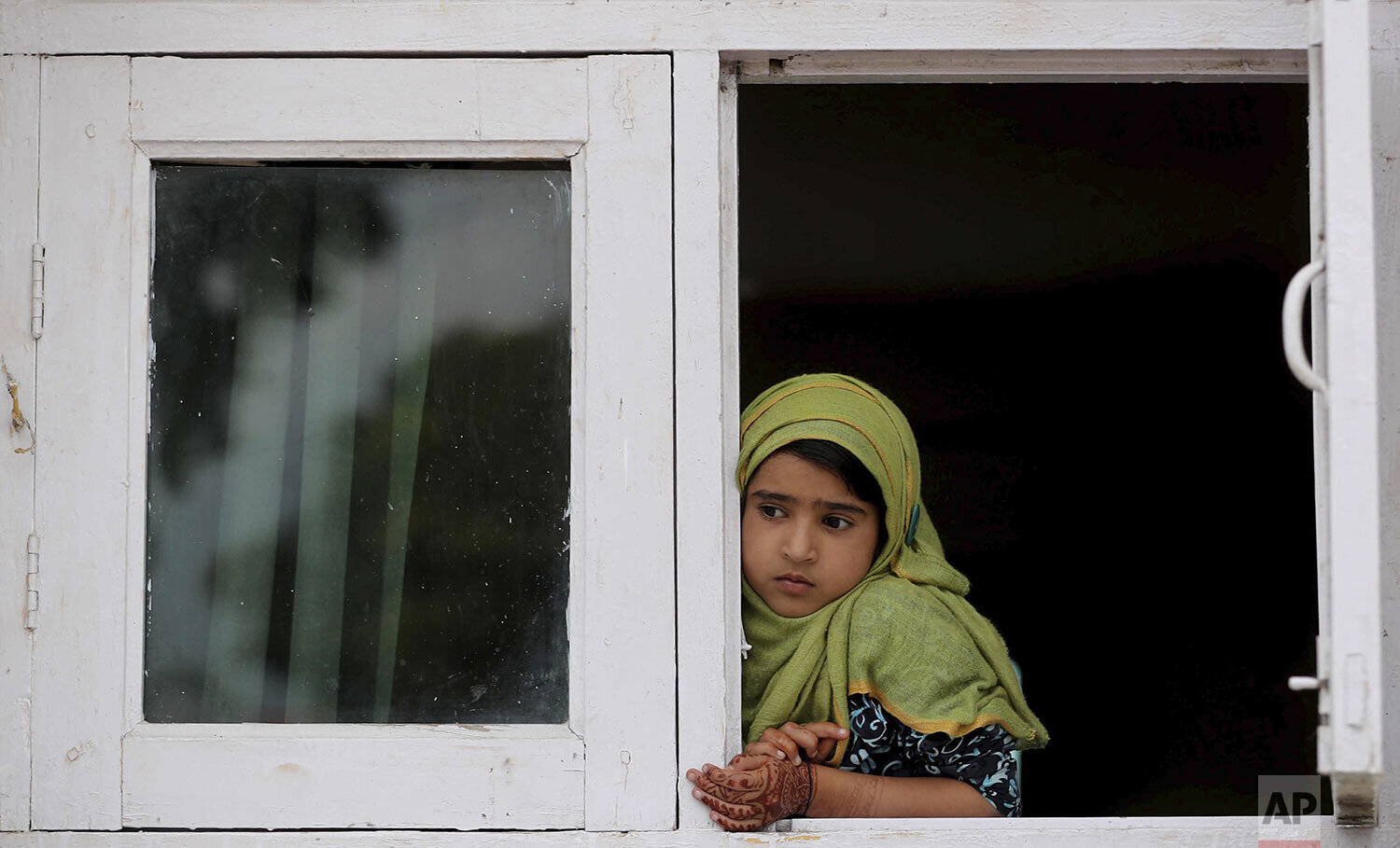 A child watches a protest from the window of a shrine in Srinagar, Indian controlled Kashmir, Friday, Aug. 30, 2019. (AP Photo/Mukhtar Khan)