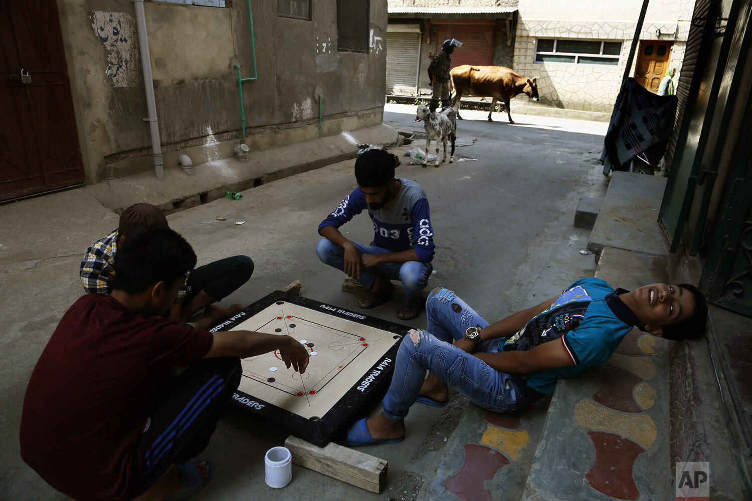 Children play carrom board as an Indian paramilitary soldier stands guard at a closed market area in Srinagar, Indian controlled Kashmir, Tuesday, Sept. 17, 2019. (AP Photo/Mukhtar Khan)