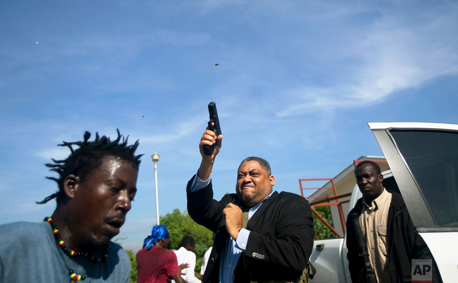 Ruling party Sen. Ralph Fethiere fires his gun outside Parliament as he arrives for a vote on the ratification of Fritz William Michel's nomination as prime minister in Port-au-Prince, Haiti, Monday, Sept. 23, 2019. Opposition members confronted ruling-party senators, and Fethiere pulled a pistol when protesters rushed at him and members of his entourage. The vote was cancelled. (AP Photo/Dieu Nalio Chery)