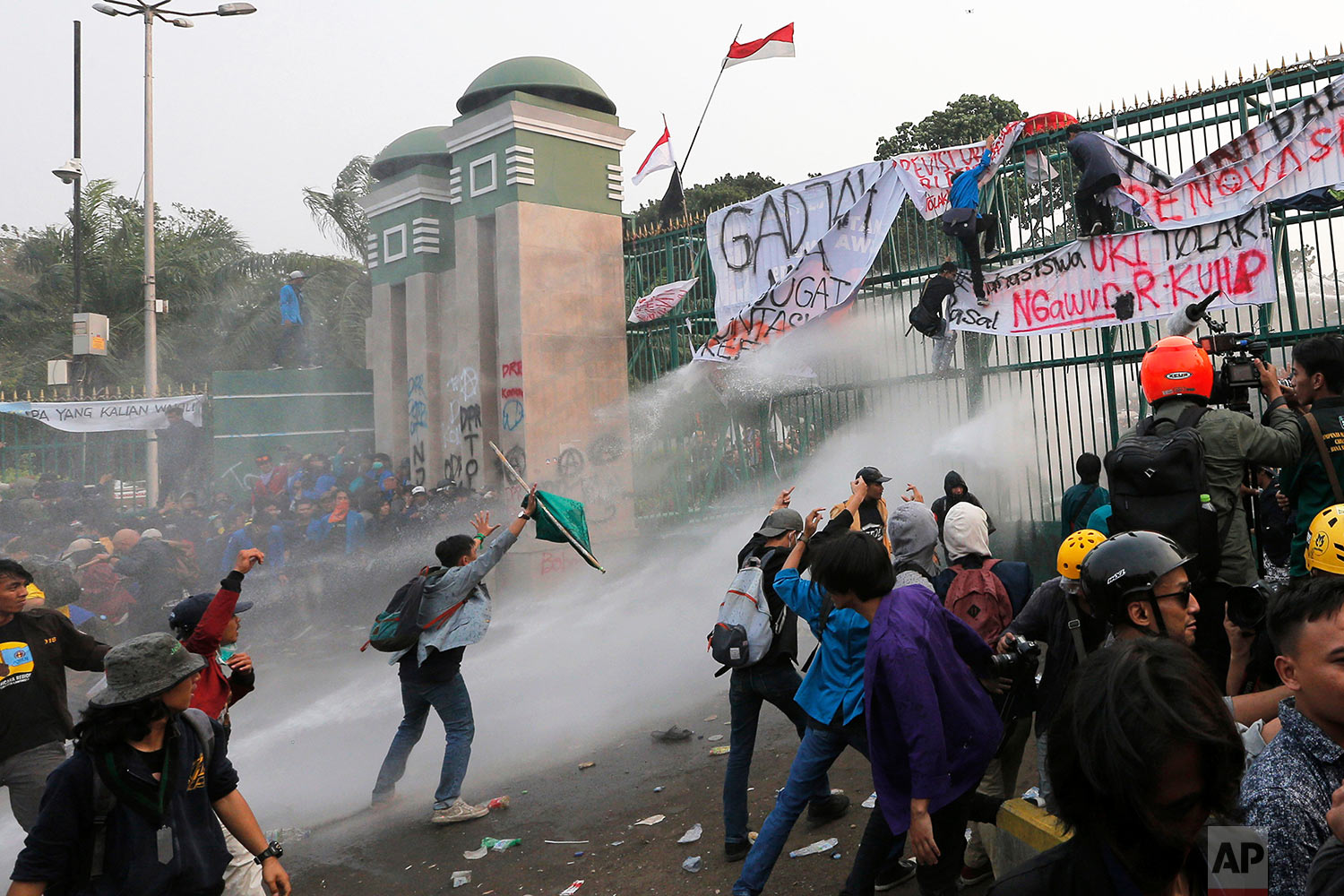 Student protesters are sprayed with water from a police water cannon truck during a protest outside parliament in Jakarta, Indonesia, Tuesday, Sept. 24, 2019. Police fired tear gas and water cannons to disperse thousands of demonstrators protesting a new law that they said has crippled Indonesia's anti-corruption agency. (AP Photo/Tatan Syuflana))