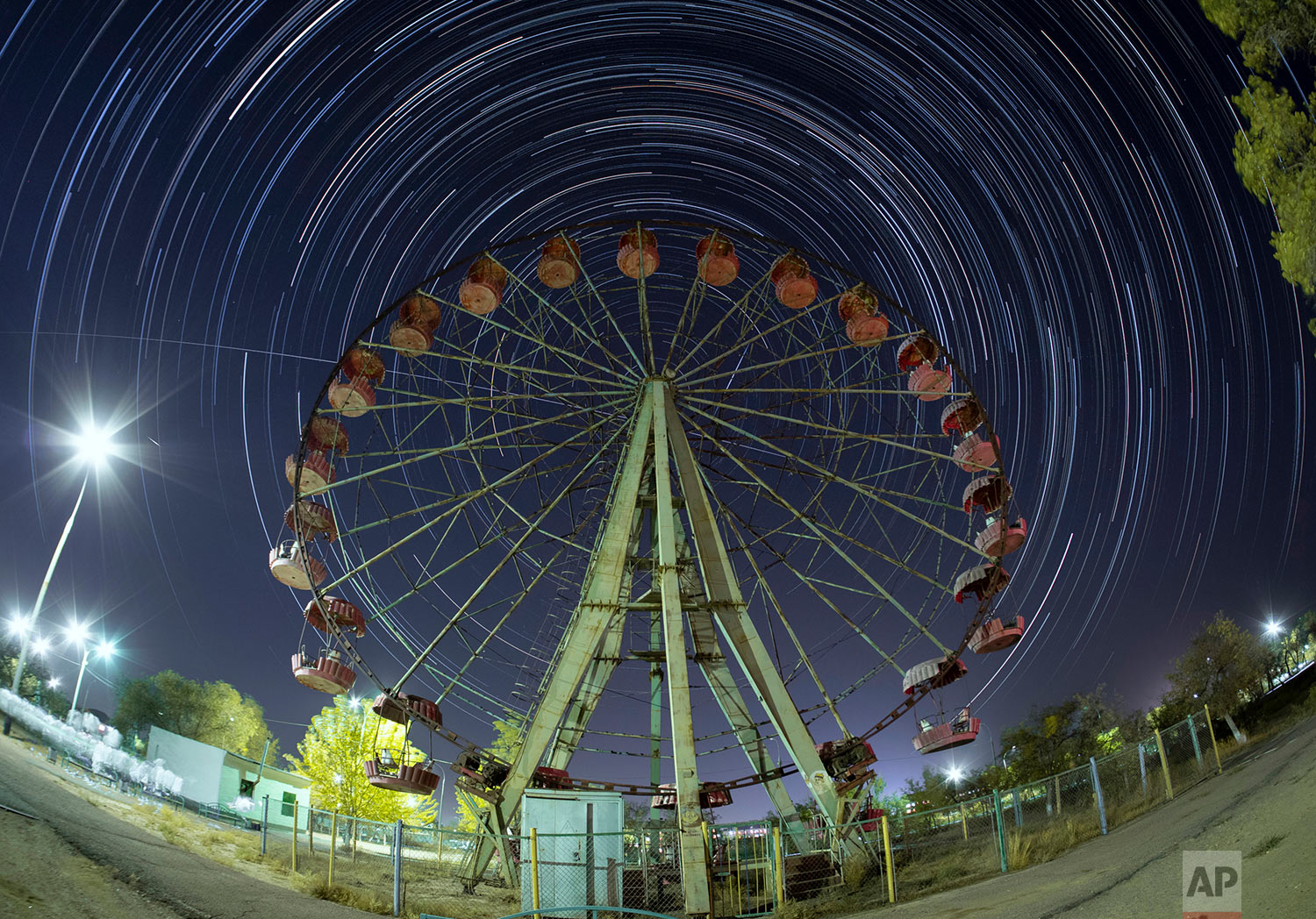 In this photo made with a three-hour-long exposure, the International Space Station moves in a line across the sky from left to right, along its orbit above a Ferris wheel in the Russian-leased Baikonur cosmodrome in Kazakhstan, Monday, Sept. 23, 2019, as stars move in an arc around the Polar Star, two days ahead of a Soyuz mission to the ISS with Russian cosmonaut Oleg Skripochka, U.S. astronaut Jessica Meir and United Arab Emirates astronaut Hazza Al Mansouri aboard. (AP Photo/Dmitri Lovetsky)