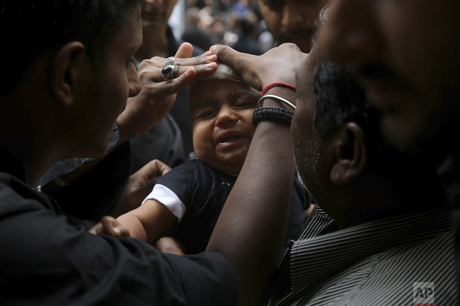 A Shiite Muslim child cries after he was given a cut on the forehead during an Ashoura procession in Hyderabad, India, Tuesday, Sept. 10, 2019. (AP Photo/Mahesh Kumar A.)