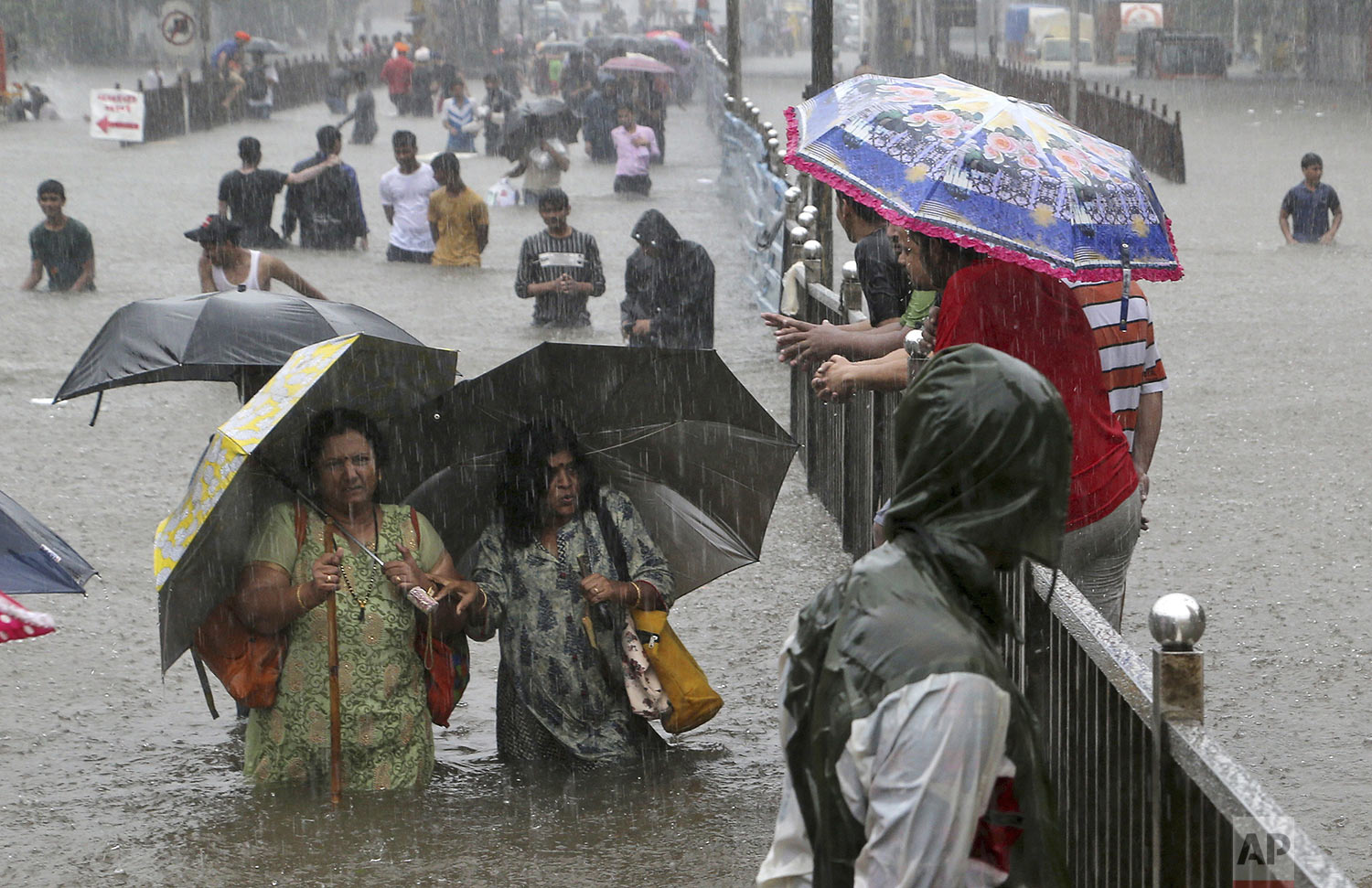 People navigate their way through a flooded street as it rains in Mumbai, India, Wednesday, Sept. 4, 2019. (AP Photo/Rajanish Kakade)