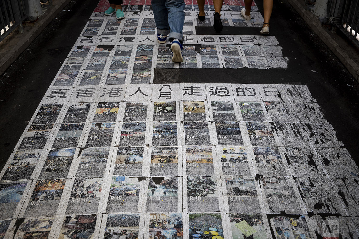 "People walk on photos showing the recent protests with the words ""The days the Hong Kong people have passed"" at a pedestrian overhead bridge in Hong Kong, Wednesday, Sept. 25, 2019. (AP Photo/Vincent Thian)"