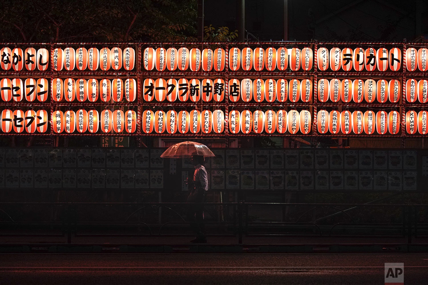 A man walks with an umbrella past lanterns in the Nakano district of Tokyo, Wednesday, Sept. 11, 2019. (AP Photo/Jae C. Hong)