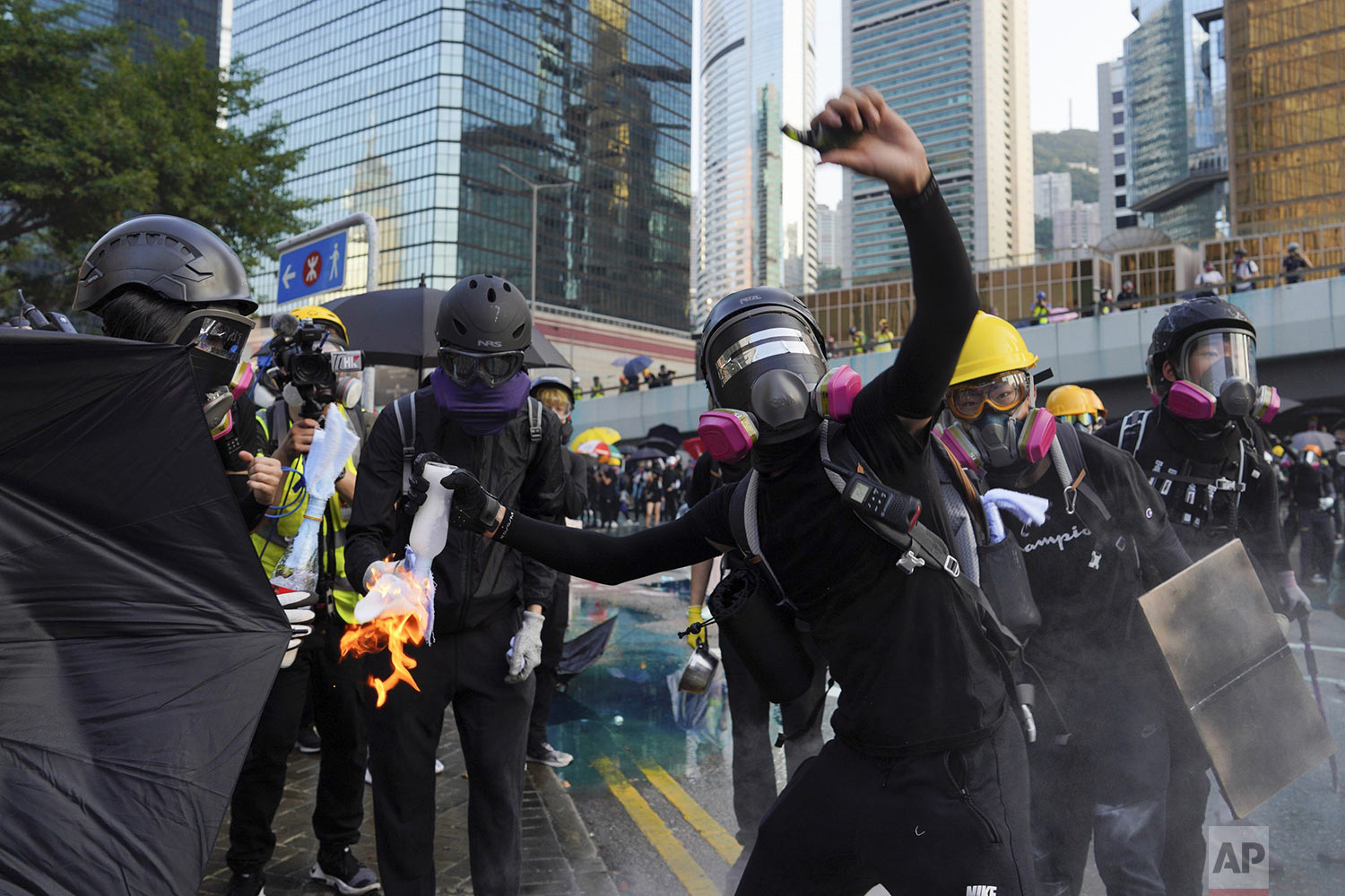 An anti-government protester throws a Molotov cocktail during a demonstration near Central Government Complex in Hong Kong, Sunday, Sept. 15, 2019. (AP Photo/Vincent Yu)