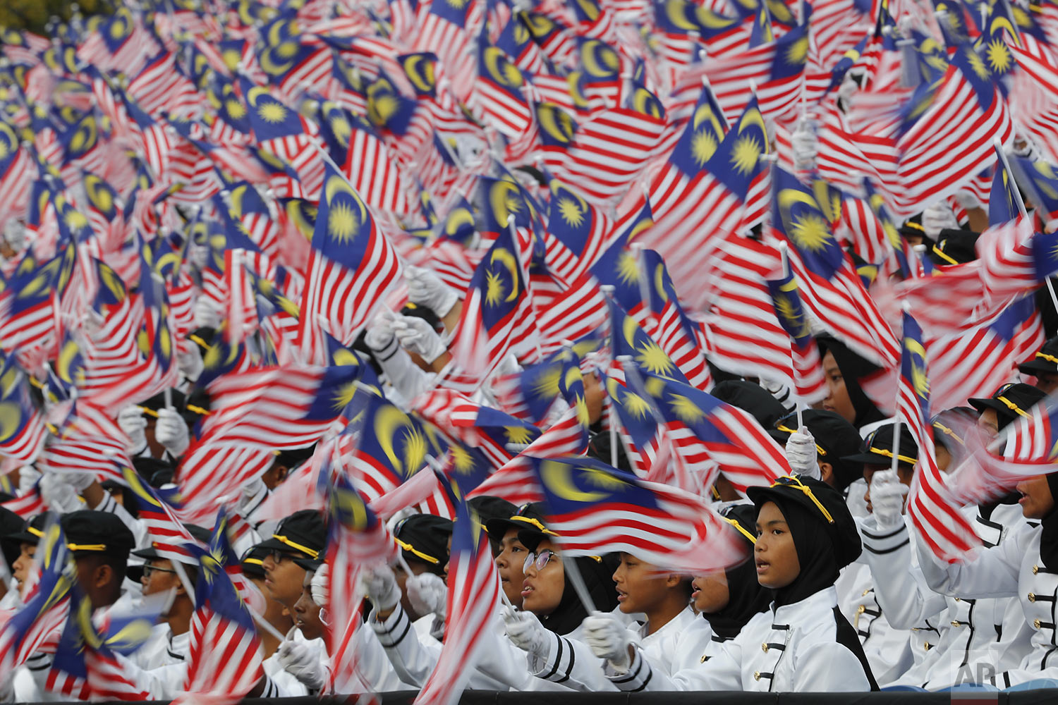 Students wave national flags during 62nd Independence Day celebrations in Putrajaya, Malaysia, Saturday, Aug. 31, 2019. (AP Photo/Vincent Thian)