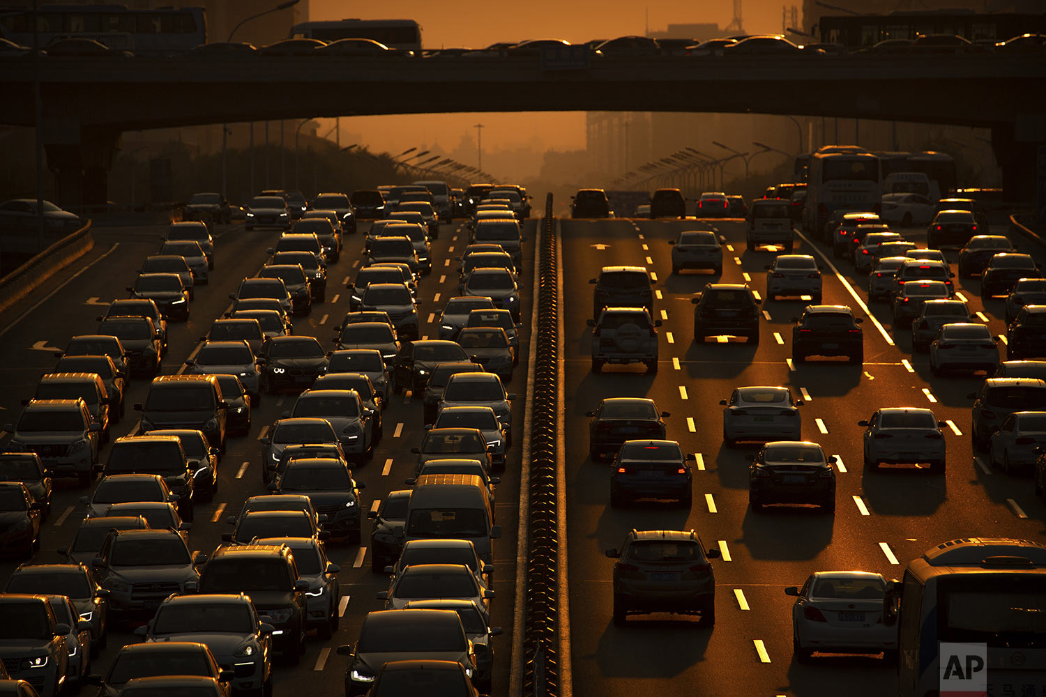 Commuters make their way along an expressway during rush hour in Beijing, Friday, Sept. 6, 2019. (AP Photo/Mark Schiefelbein)
