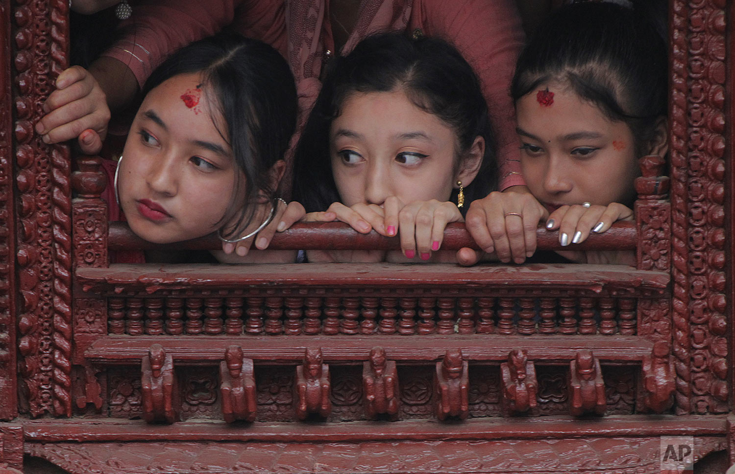 Former living goddess Kumari, center, watches the Indra Jatra festival, an eight-day festival that honors Indra, the Hindu god of rain, in Kathmandu, Nepal, Friday, Sept. 13, 2019. (AP Photo/Niranjan Shrestha)