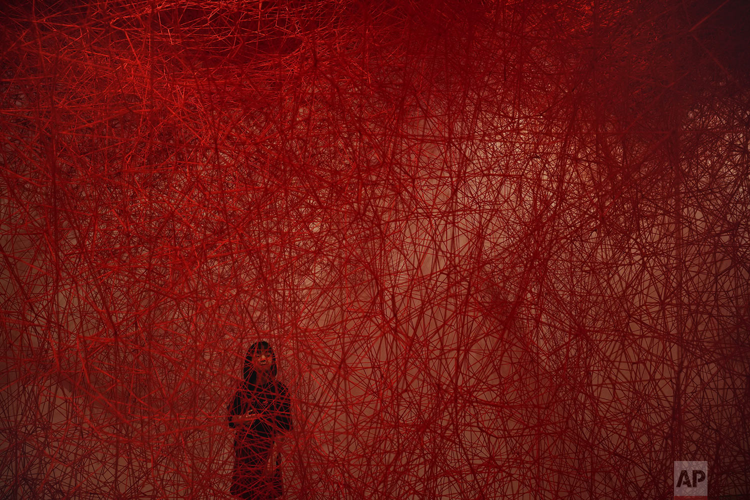 "A woman looks at Chiharu Shiota's art installation titled ""Uncertain Journey"" at the Mori Art Museum, in Tokyo, Thursday, Sept. 19, 2019. (AP Photo/Jae C. Hong)"