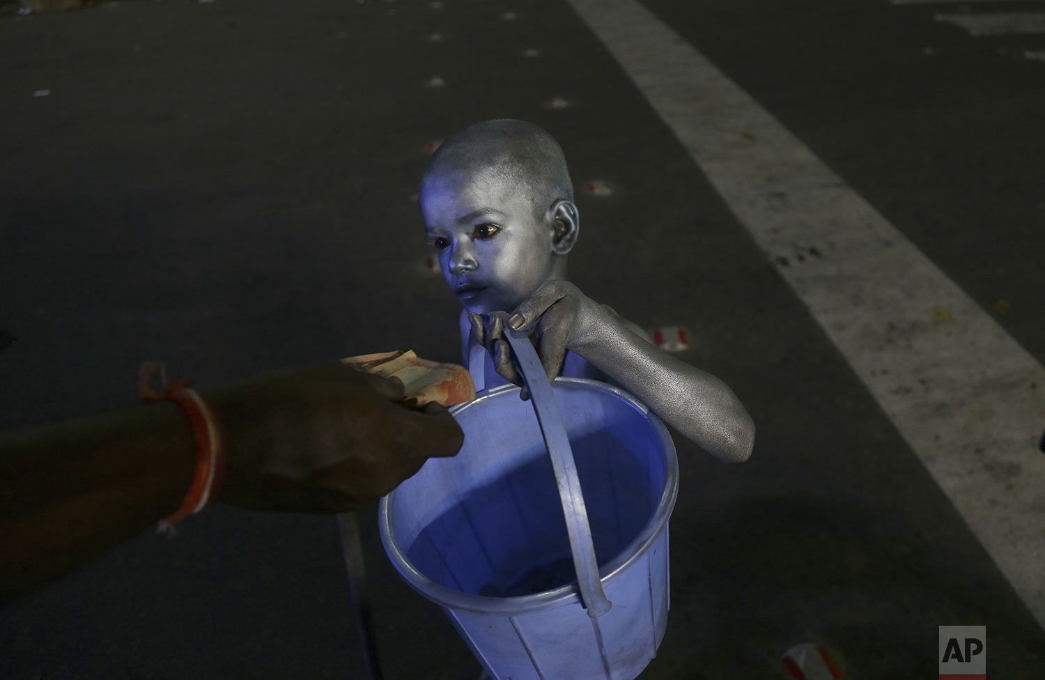 A young boy with his body painted and dressed as Mahatma Gandhi seek alms at a traffic intersection in Hyderabad, India, Tuesday, Sept.10, 2019.  (AP Photo/Mahesh Kumar A.)