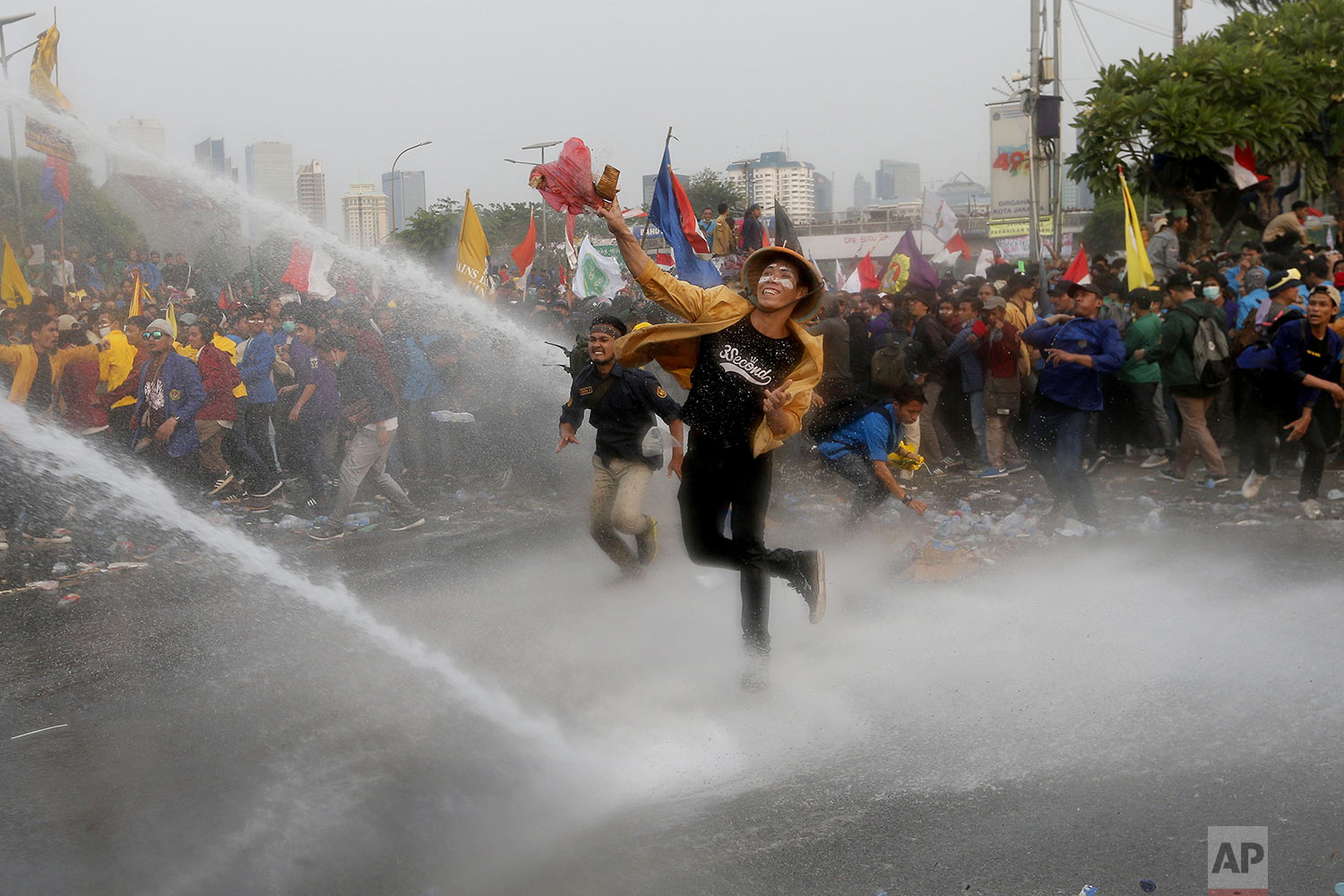 Student protesters hurl objects as they are sprayed by a police water cannon truck during a protest outside the parliament in Jakarta, Indonesia, Tuesday, Sept. 24, 2019.  (AP Photo/Tatan Syuflana)