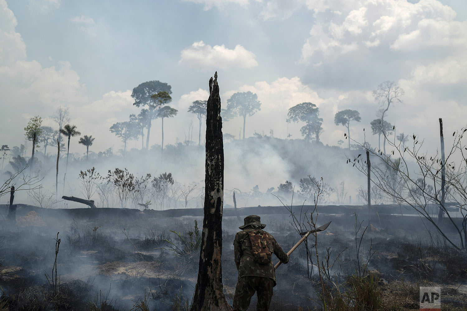 A Brazilian soldier puts out fires at the Nova Fronteira region in Novo Progresso, Brazil, Tuesday, Sept. 3, 2019. Brazilian President Jair Bolsonaro sent the military to help extinguish some fires. Last week, he passed a decree banning most fires for land-clearing for a period of 60 days, although he later limited the ban to the Amazon. (AP Photo/Leo Correa)