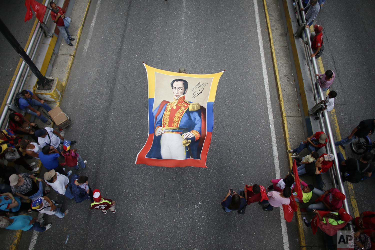Supporters of President Nicolas Maduro holds a banner of Venezuela's independence hero Simon Bolivar during a rally celebrating 11 years of the Socialist Party of Venezuela' youth in Caracas, Venezuela, Thursday, Sept. 12, 2019. (AP Photo/Ariana Cubillos)