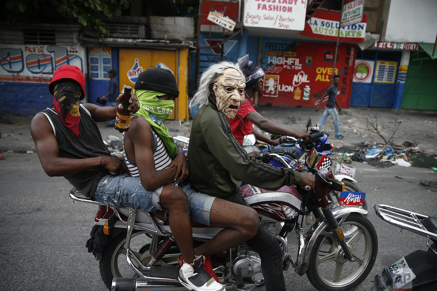 Masked protestors ride a motorcycle in Port-au-Prince, Haiti, Monday, Sept. 30, 2019. Demonstrators set fires Monday and chanted calls for Haiti's President Jovenel Moise to resign, the latest in a series of protests aimed at pushing Moise from office. (AP Photo/Rebecca Blackwell)