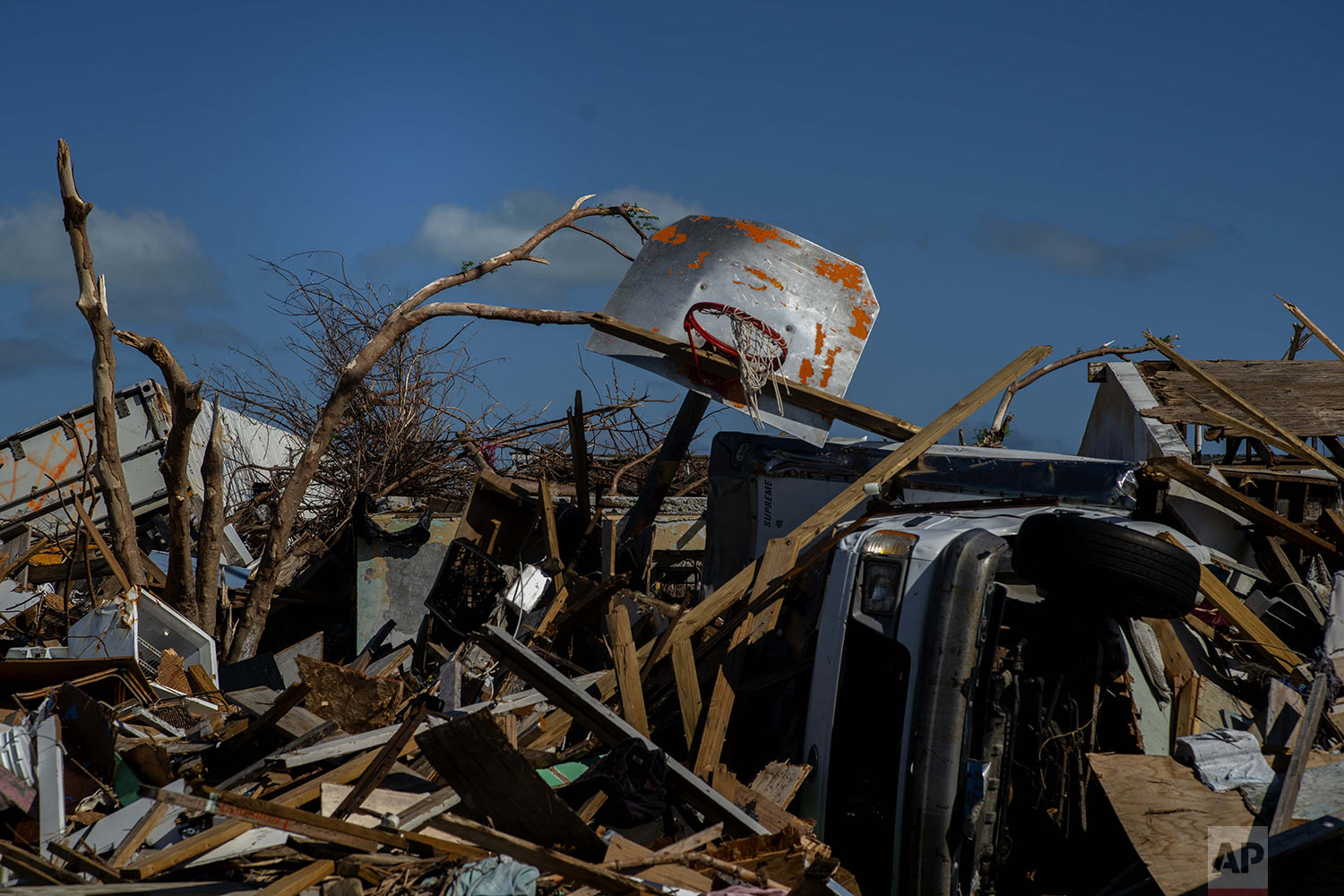 A basketball board is seen next to a car among the debris left by Hurricane Dorian, in a neighborhood destroyed by Hurricane Dorian, in Abaco, Bahamas, Friday, Sept. 27, 2019. Dorian hit the northern Bahamas on Sept. 1, with sustained winds of 185 mph (295 kph), unleashing flooding that reached up to 25 feet (8 meters) in some areas. (AP Photo/Ramon Espinosa)