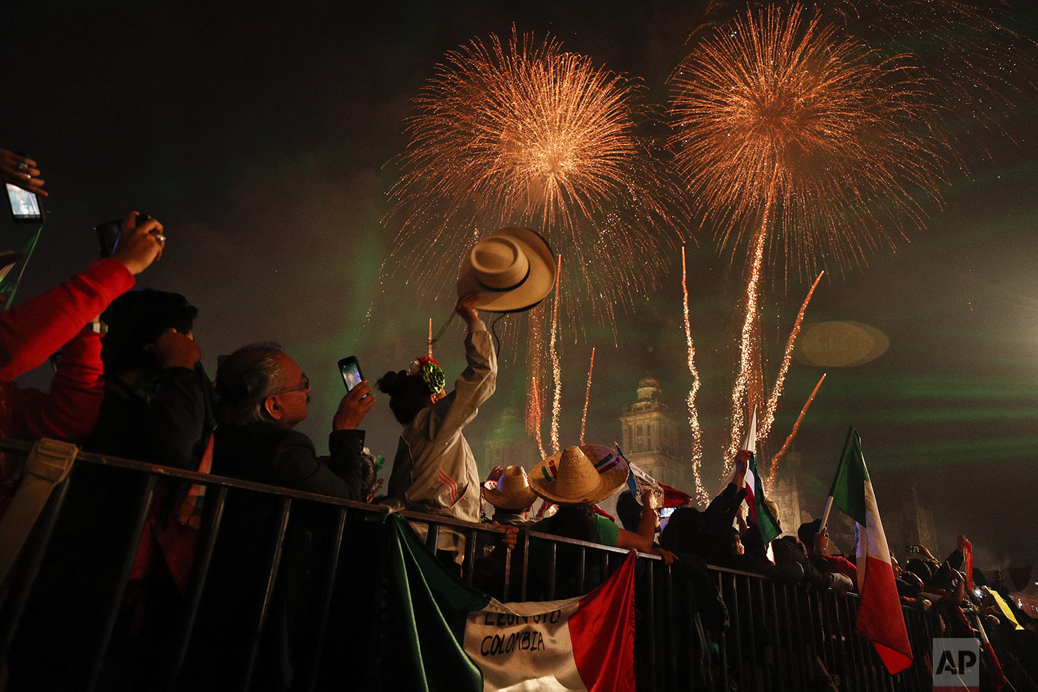 """Revelers celebrate as fireworks explode over the Metropolitan Cathedral after President Andres Manuel Lopez Obrador gave the annual independence shout from the balcony of the National Palace to kick off Independence Day celebrations in Mexico City, late Sunday, Sept. 15, 2019. Every year the Mexican president marks the """"Grito de Dolores,"""" commemorating the 1810 call to arms by priest Miguel Hidalgo that began the struggle for independence from Spain, achieved in 1821. (AP Photo/Rebecca Blackwell)"""