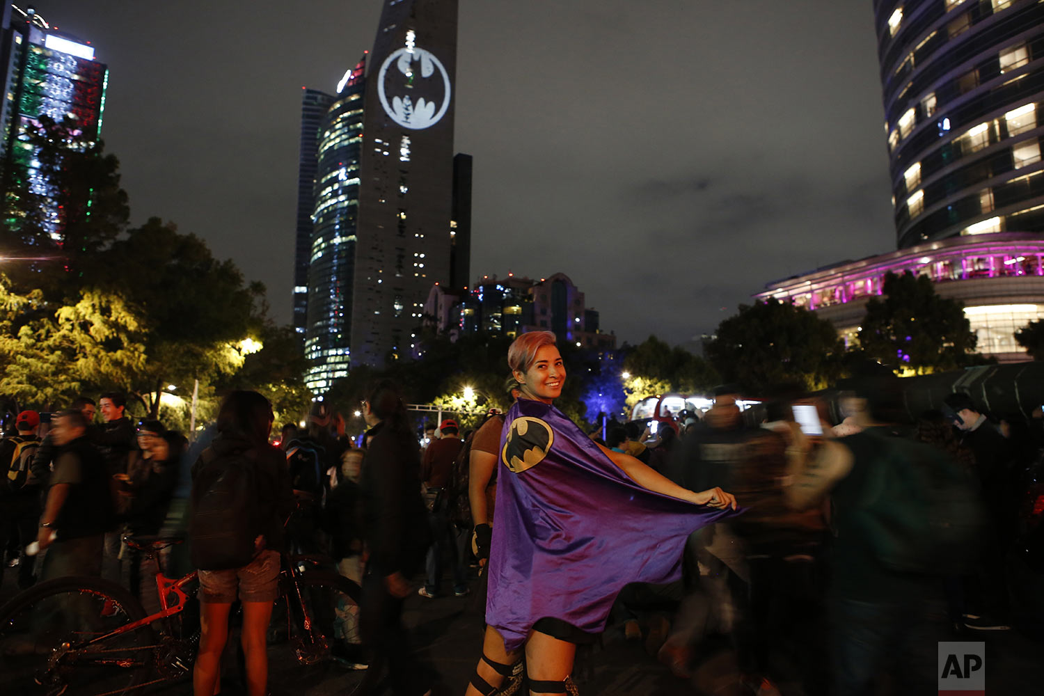 Stephanie Salgado poses with her cape during the lighting of a Bat-signal commemorating Batman's 80th anniversary in Mexico City, on Saturday, Sept. 21, 2019. (AP Photo/Ginnette Riquelme)