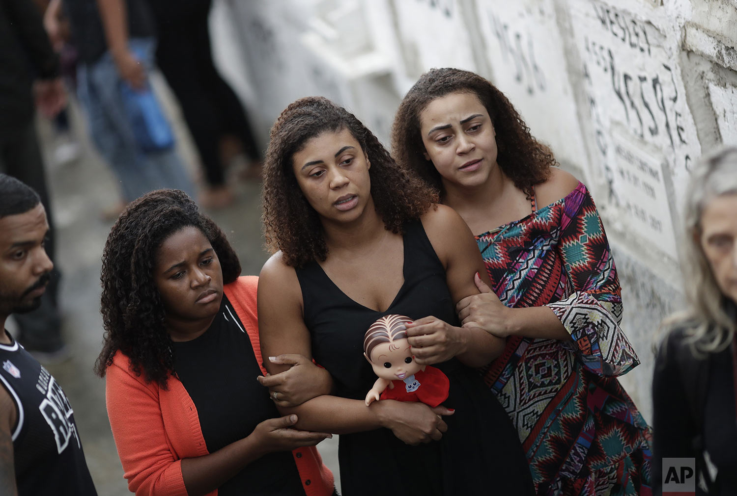 Vanessa Francisco Sales holds the doll of her 8-year-old daughter Ágatha Sales Felix during her daughter's burial at the cemetery in Rio de Janeiro, Brazil, Sunday, Sept. 22, 2019. Félix was hit by a stray bullet Friday amid what police said was a shootout with suspected criminals. However, residents say there was no shootout, and blame police. (AP Photo/Silvia Izquierdo)