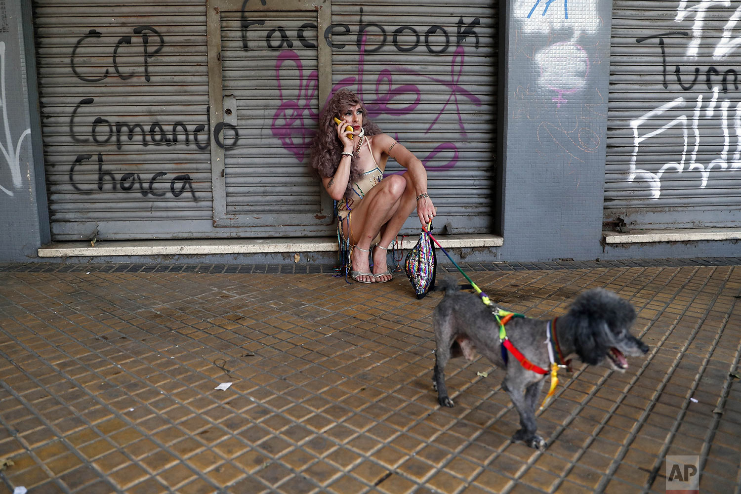 A trans woman takes a call on the sidelines of the LGTBI march in Asuncion, Paraguay, Saturday, Sept. 28, 2019. The marchers are requesting the government approve the legal name changes from male to female of trans members in their community. Paraguay is one of the most sexually conservative countries in Latin America. (AP Photo/Jorge Saenz)
