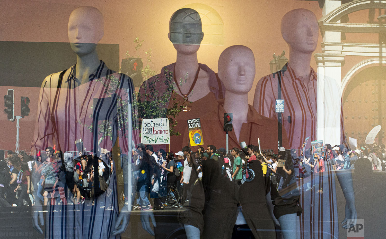 Demonstrators taking part in a global protest on climate change are reflected on a clothing store window, in Santiago, Chile, on Friday, Sept. 20, 2019. Throughout the world Friday, young people banded together to demand that world leaders headed to a United Nations summit in New York step up their efforts to combat climate change. (AP Photo/Esteban Felix)
