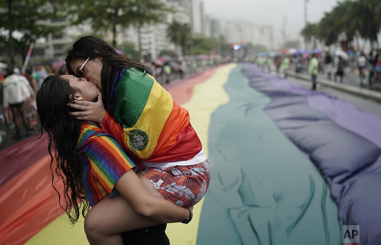 People kiss during the annual gay pride parade along Copacabana beach in Rio de Janeiro, Brazil, Sunday, Sept. 22, 2019. (AP Photo/Leo Correa)
