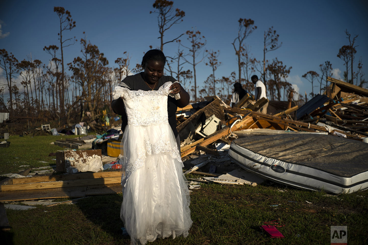 Synobia Reckley holds up the dress her niece wore as a flower girl at her wedding, as she goes through valuables in the rubble of her home destroyed one week ago by Hurricane Dorian in Rocky Creek East End, Grand Bahama, Bahamas, Sunday, Sept. 8, 2019.  Synobia, 25, married two days after Hurricane Mathew in 2016, which passed over her home without doing serious damage. (AP Photo/Ramon Espinosa)