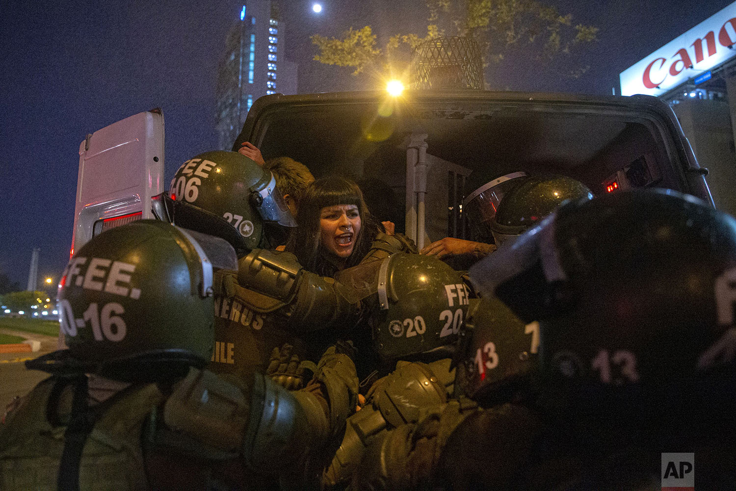 A woman is detained by police during a feminist protest marking the 46th anniversary of the military coup that ousted the late President Salvador Allende, in Santiago, Chile, Wednesday, Sept. 11, 2019. (AP Photo/Esteban Felix)