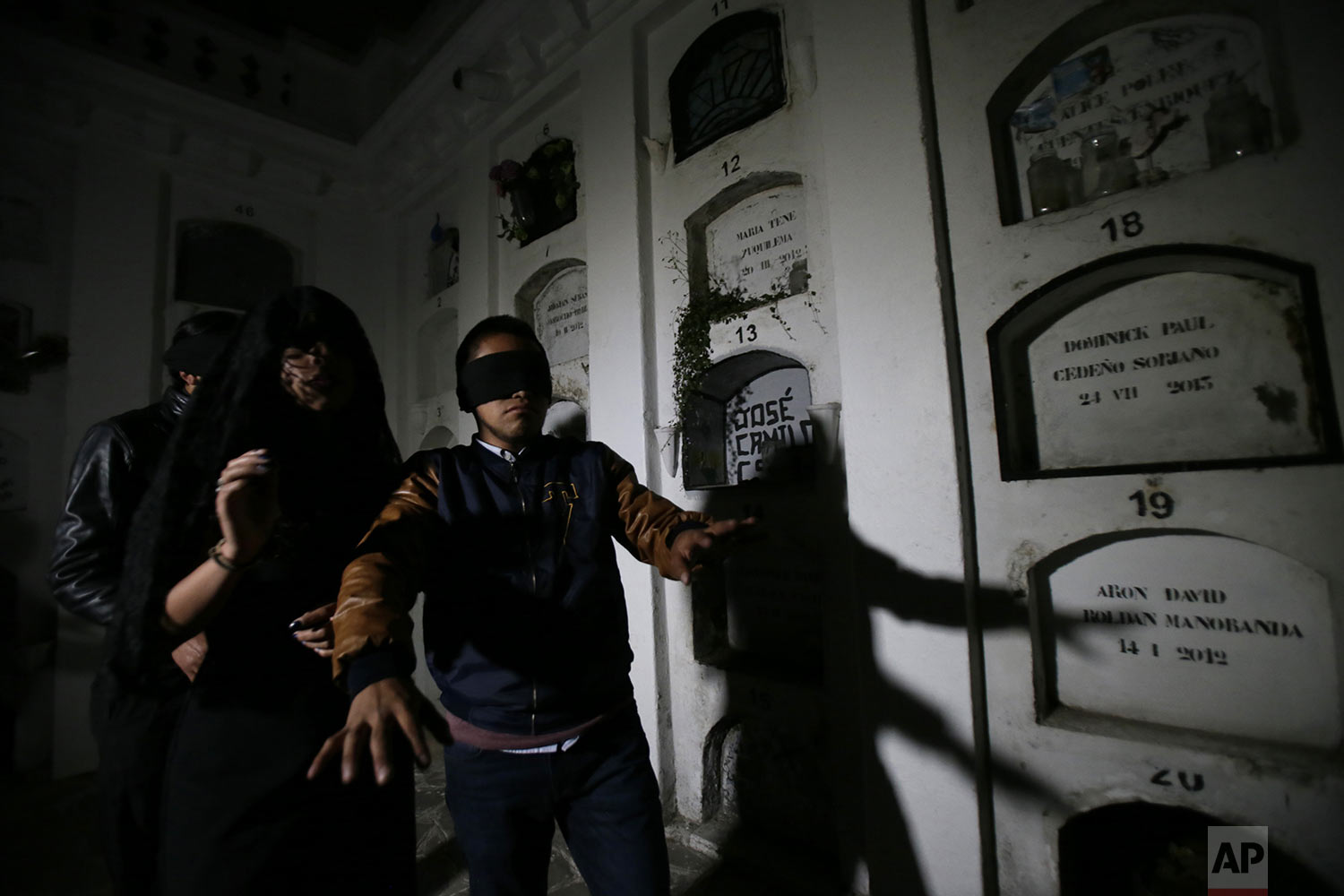 """Blindfolded tourists walk through El Tejar cemetery in Quito, Ecuador, Wednesday, Sept. 11, 2019. They're there to get a taste of death while still alive, spending part of the night in a dark crypt at the El Tejar cemetery, the latest example of the so-called """"necro tourism"""" trend luring those with a keenness for the macabre. (AP Photo/Dolores Ochoa)"""