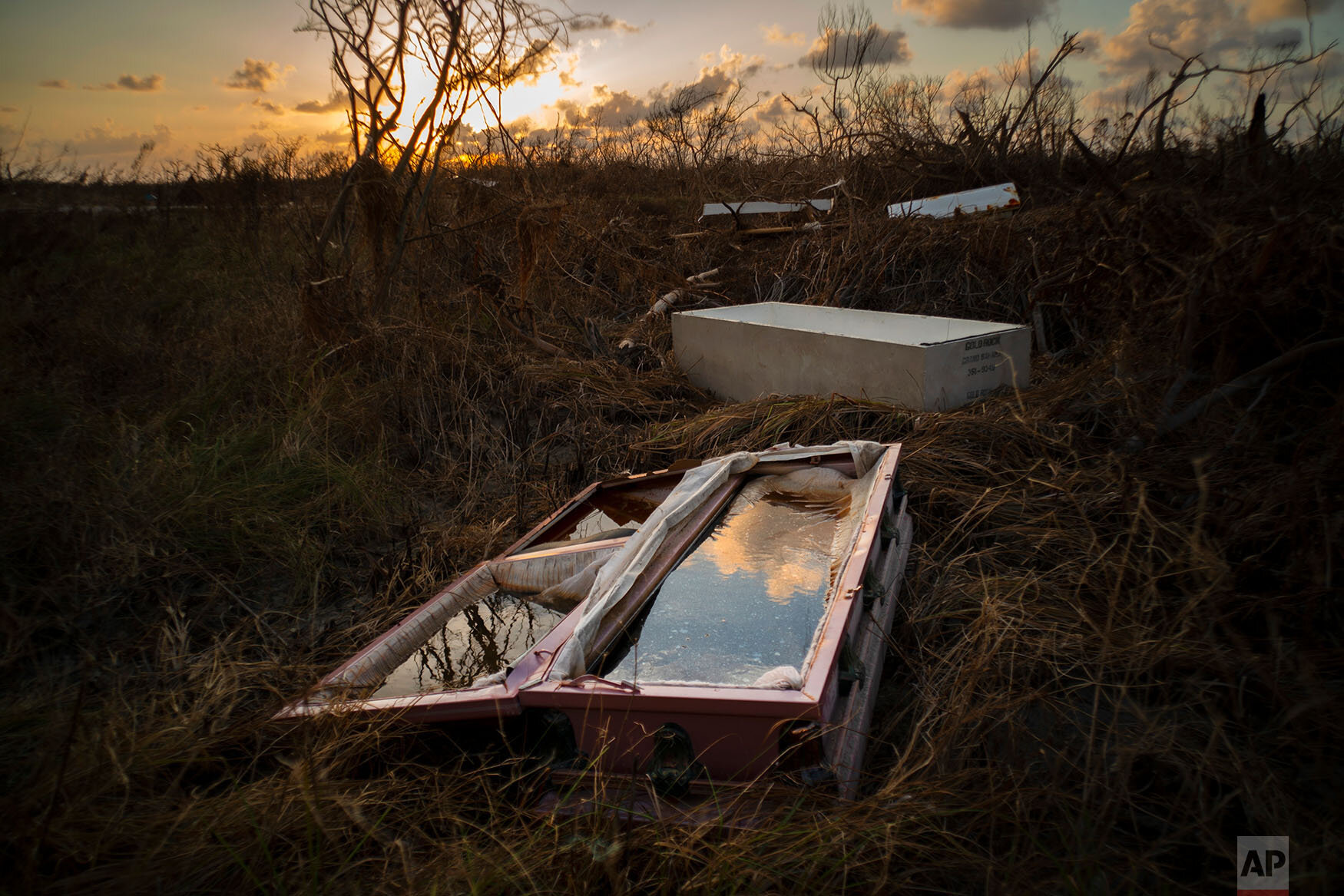 A shattered and water-filled coffin lays exposed to the elements in the aftermath of Hurricane Dorian, at the cemetery in Mclean's Town, Grand Bahama, Bahamas, Wednesday Sept. 11, 2019.  (AP Photo/Ramon Espinosa)