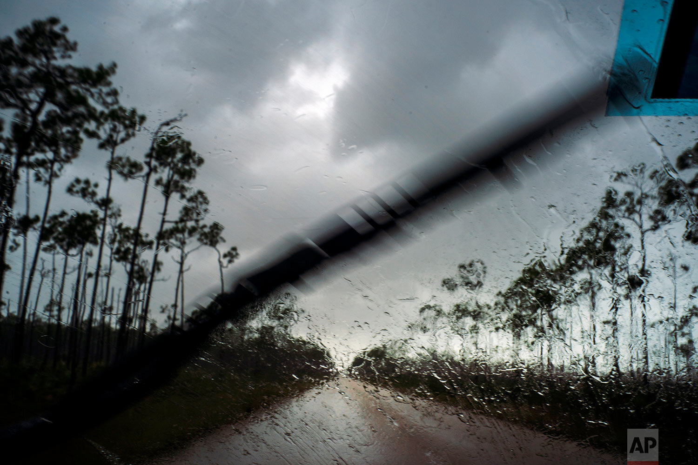 A car returns to the capital under the previous rain before the arrival of Hurricane Dorian in Freeport, Grand Bahama, Bahamas, Sunday Sept. 1, 2019. (AP Photo/Ramon Espinosa)