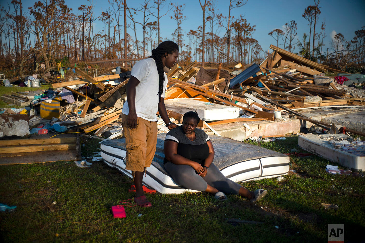 Synobia Reckley pauses on a wet mattress as her husband Dexter Edwards consoles her amid the remains of their home destroyed by Hurricane Dorian in Rocky Creek East End, Grand Bahama, Bahamas, Sunday, Sept. 8, 2019. The couple married two days after Hurricane Mathew hit in 2016 but did not do serious damage. (AP Photo/Ramon Espinosa)