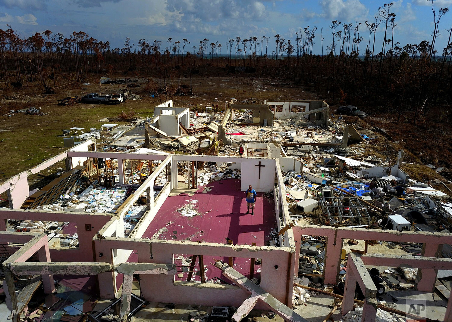 """Pastor Jeremiah Saunders poses for a photo among the ruins of his church that was destroyed by Hurricane Dorian, in High Rock, Grand Bahama, Bahamas, Wednesday Sept. 11, 2019. Jeremiah says """"I spoke to the water: 'Peace, be still.' It never listened,"""" Saunders said with a wide smile and then grew serious as he focused on the task that tens of thousands of Bahamians now face on two islands devastated by the Category 5 storm: the clean-up. (AP Photo / Ramon Espinosa)"""