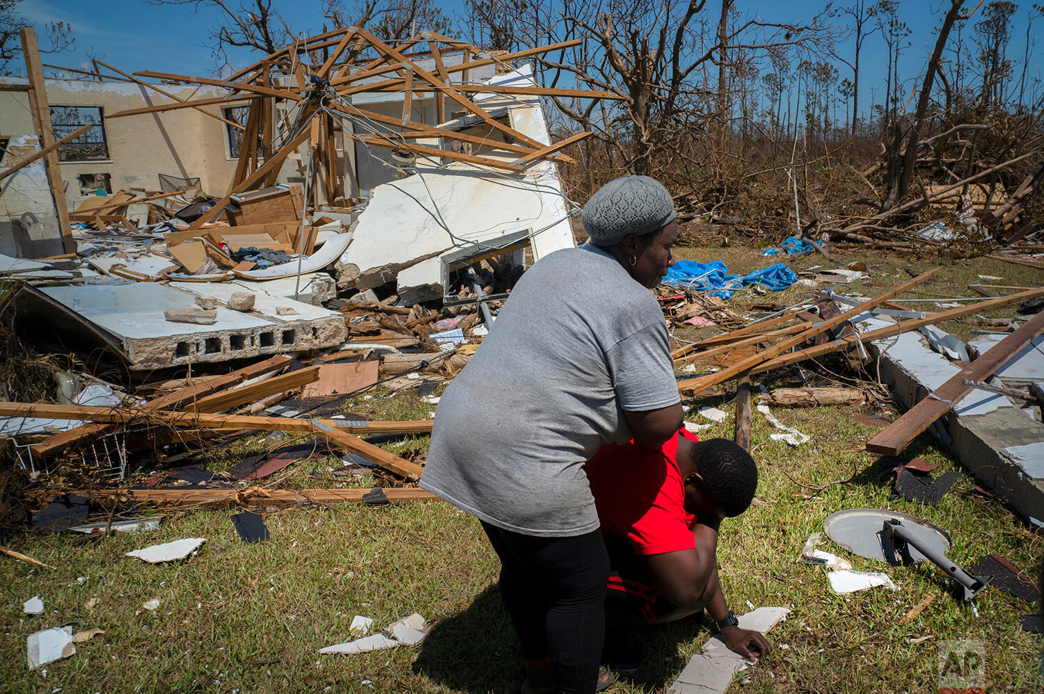 A woman comforts a man who cries after discovering his shattered house and not knowing anything about his 8 relatives who lived in the house, missing in the aftermath of Hurricane Dorian, in High Rock, Grand Bahama, Bahamas, Thursday, Sept. 5, 2019. (AP Photo/Ramon Espinosa)