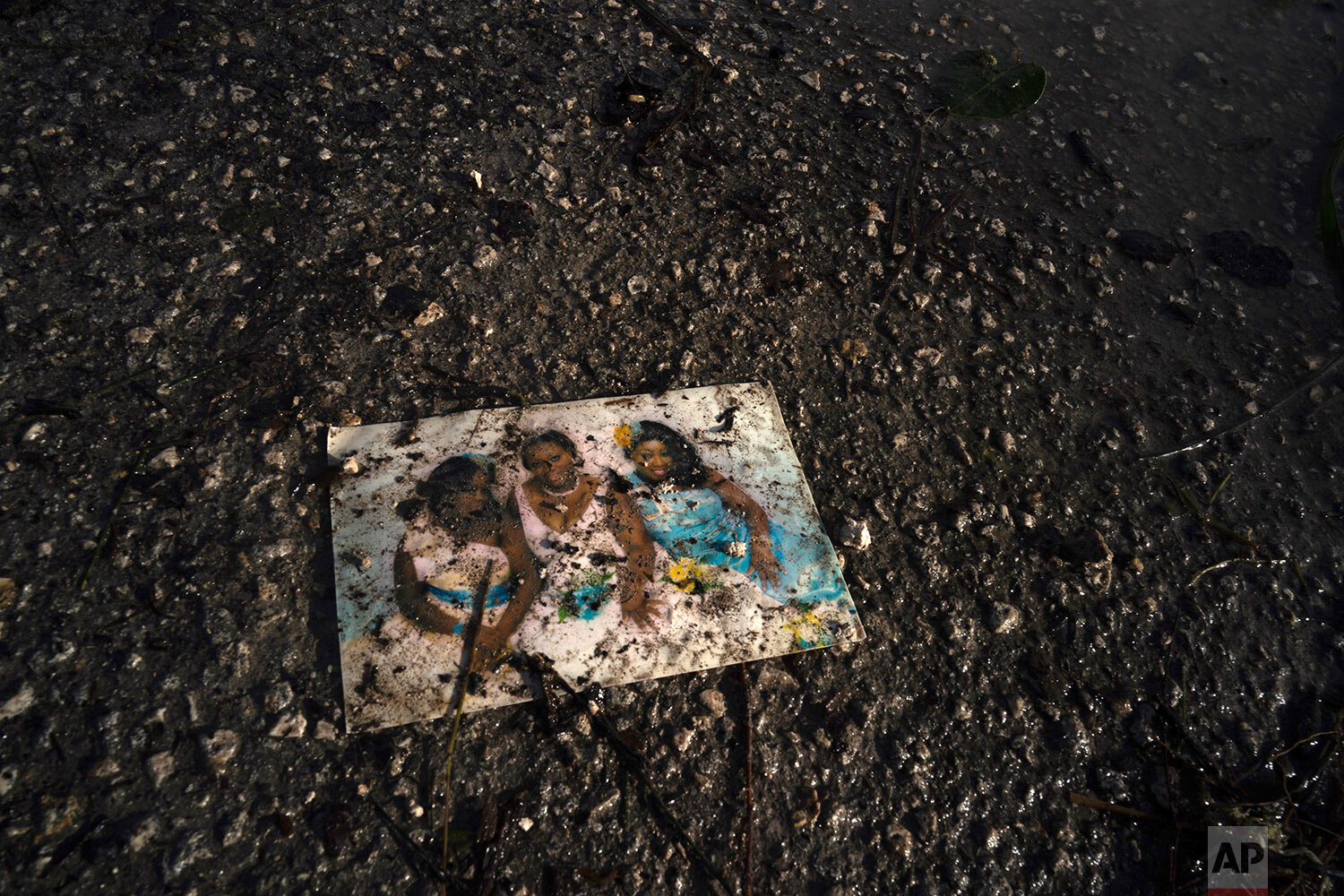 A family photo lies on a muddied road in the aftermath of Hurricane Dorian in Pine Bay, near Freeport, Bahamas, Wednesday, Sept. 4, 2019.  (AP Photo/Ramon Espinosa)