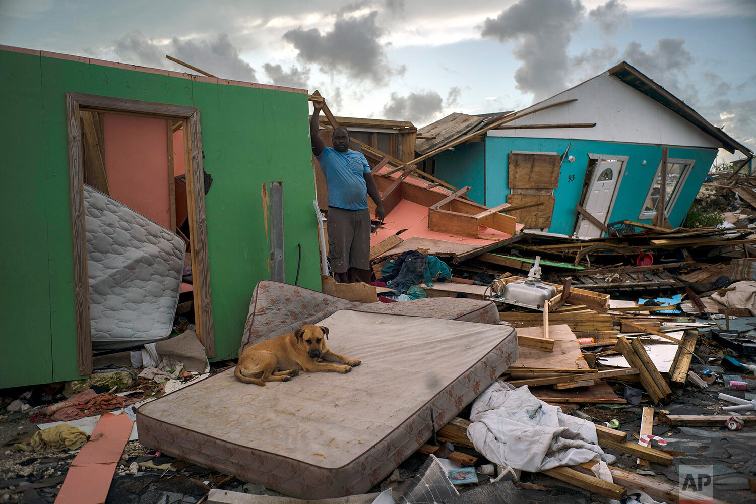 A man stands next to a destroyed house as a dog named Francoise rests on a mattress in the rubble left by Hurricane Dorian in Abaco, Bahamas, Monday, Sept. 16, 2019. (AP Photo/Ramon Espinosa)