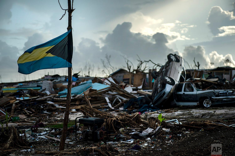 A Bahamas flag flies tied to a sapling, amidst the rubble left by Hurricane Dorian in Abaco, Bahamas, Monday, Sept. 16, 2019. (AP Photo/Ramon Espinosa)