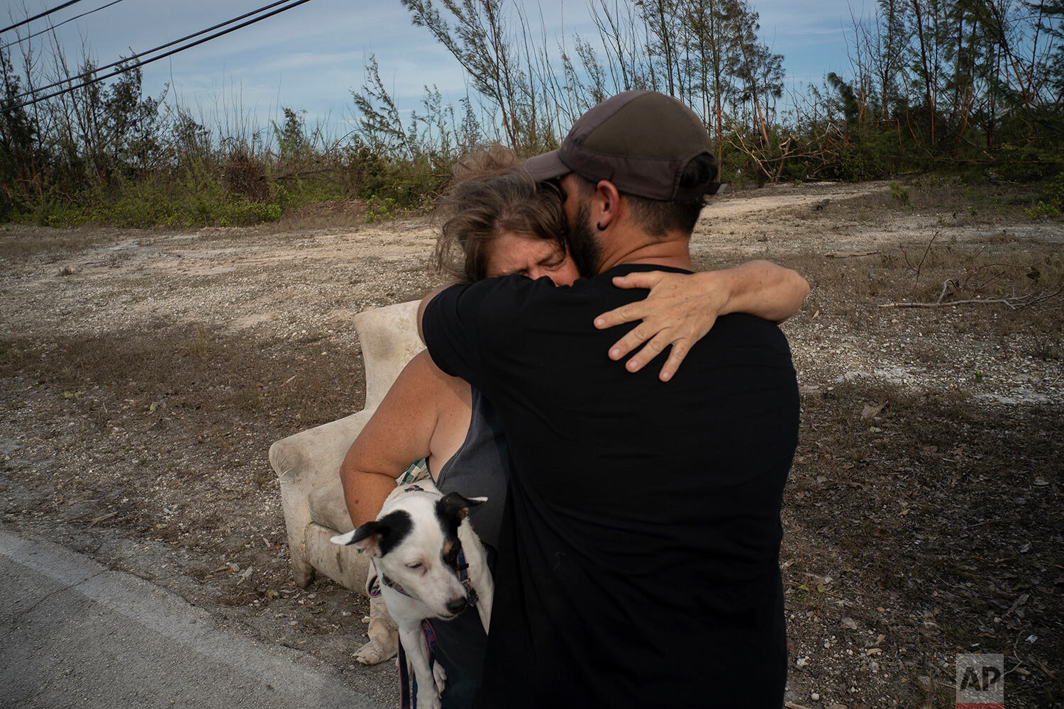 Sissel Mosvold embraces a volunteer who helped rescue her mother from her home, flooded by the waters of Hurricane Dorian, in the outskirts of Freeport, Bahamas, Wednesday, Sept. 4, 2019. (AP Photo/Ramon Espinosa)