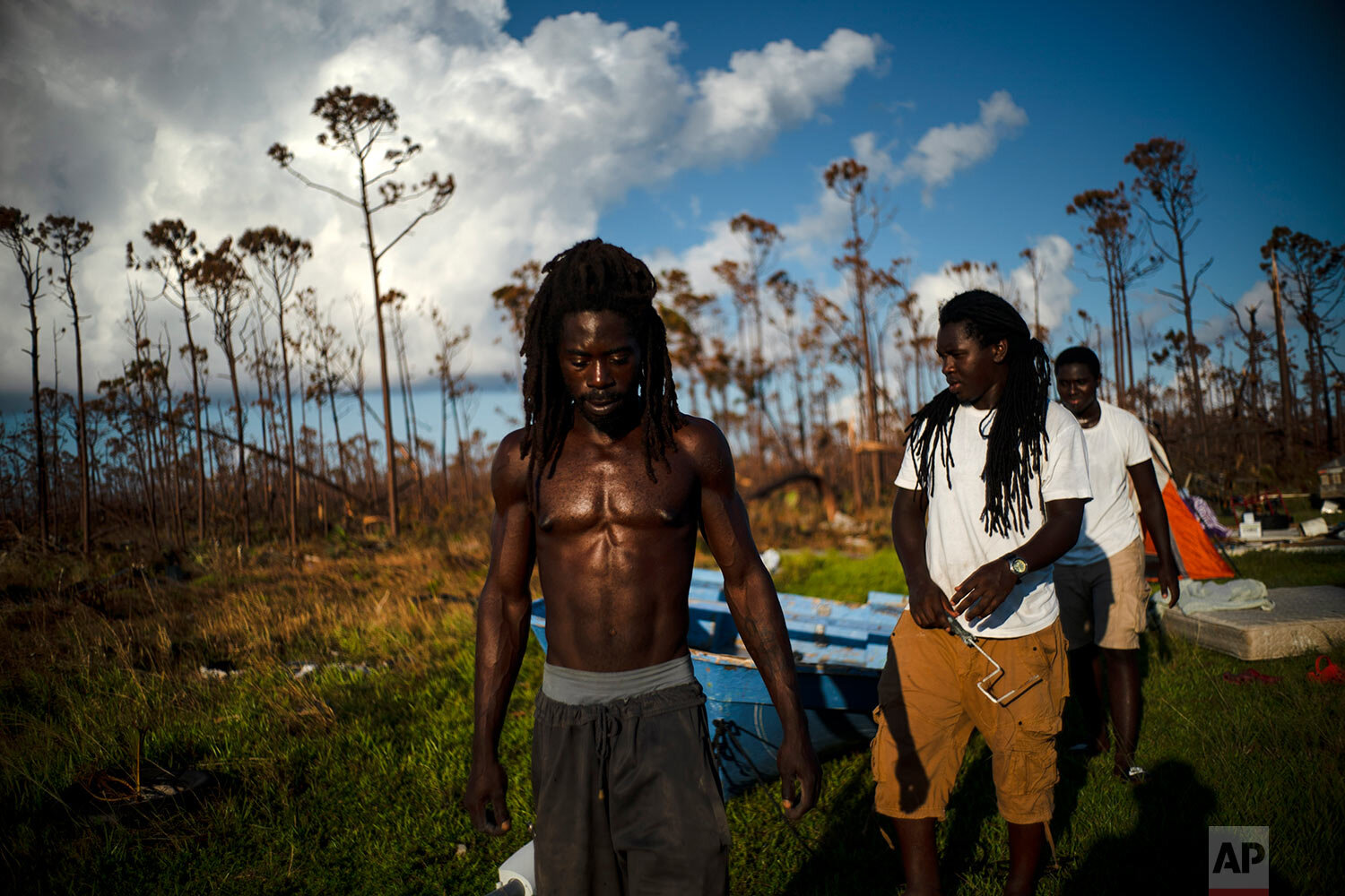 """Dexter Edwards, front, his brother Nathanael Edwards right, and his cousin Valentino Ingraham walk amid one of their family's homes destroyed by Hurricane Dorian in Rocky Creek East End, Grand Bahama, Bahamas, Sunday, Sept. 8, 2019. """"Right now, ain't much joy. You just gotta try to keep your head up,"""" Edwards said. """"There's always a future. Only thing we can do right now is rebuild, rebuild and try to move forward."""" (AP Photo/Ramon Espinosa)"""