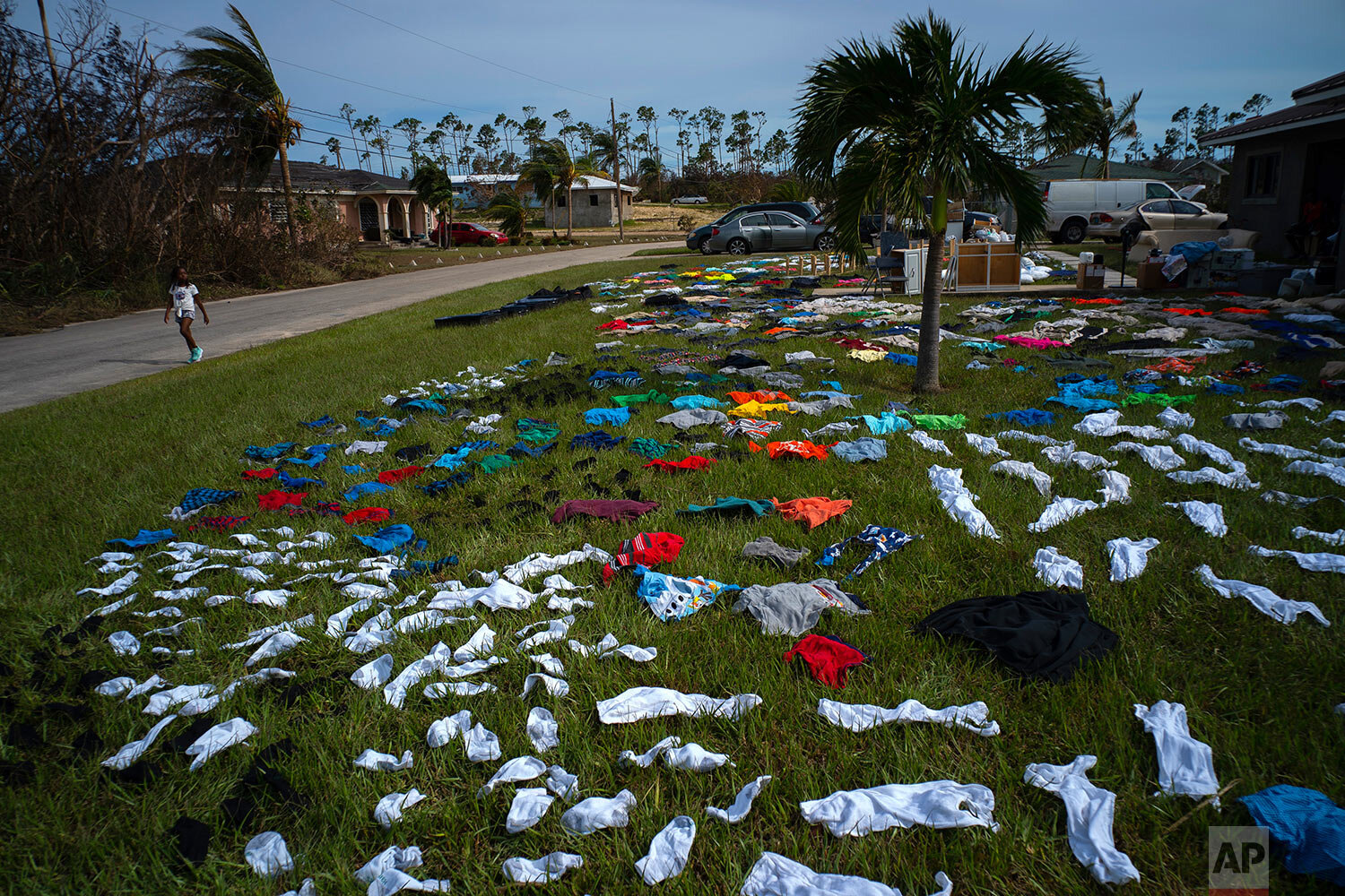 A child walks past clothes laid out to dry on a field in the aftermath of Hurricane Dorian, in the Arden Forest neighborhood of Freeport, Bahamas, Wednesday, Sept. 4, 2019. (AP Photo/Ramon Espinosa)