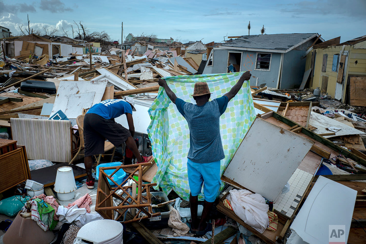 Immigrants from Haiti recover their belongings from the rubble in their destroyed homes, in the aftermath of Hurricane Dorian in Abaco, Bahamas, Monday, Sept. 16, 2019.  (AP Photo/Ramon Espinosa)