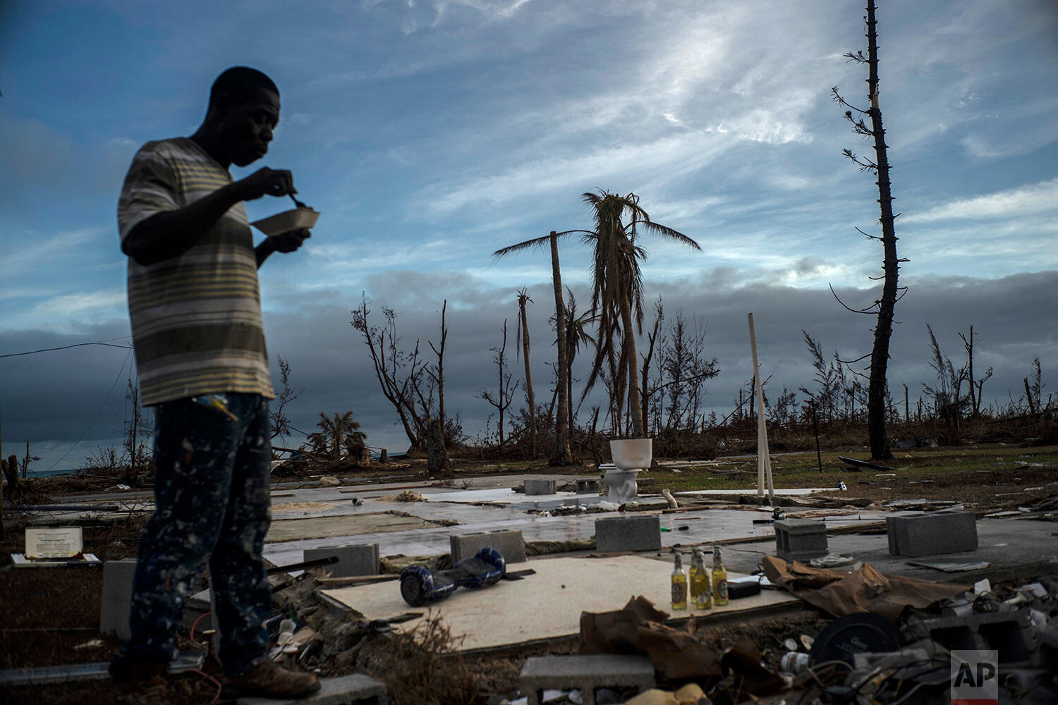 Jeffrey Roberts, 49, eats a plate of food while searching through the rubble of his relatives' home which was destroyed by Hurricane Dorian in Pelican Point, Grand Bahama, Bahamas, Saturday, Sept. 14, 2019.  (AP Photo/Ramon Espinosa)