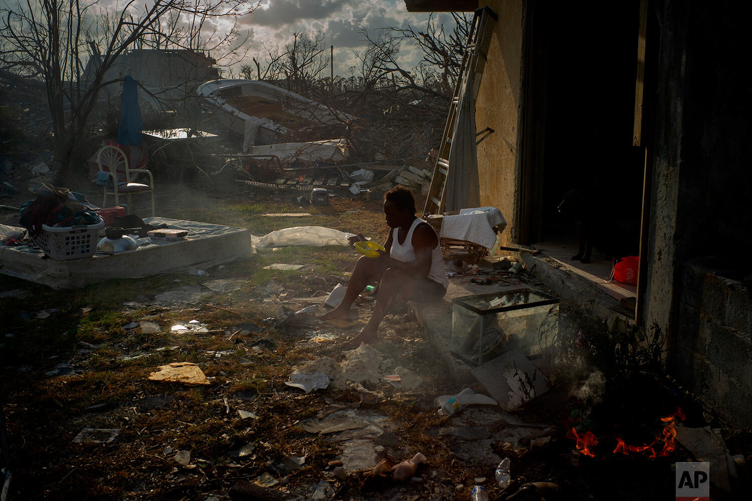 Tereha Davis, 45, eats a meal of rice as she sits among the remains of her shattered home, in the aftermath of Hurricane Dorian in McLean's Town, Grand Bahama, Bahamas, Wednesday Sept. 11, 2019. She and others said they had not seen any government officials and have only received food and water from some nonprofit organizations. (AP Photo/Ramon Espinosa)