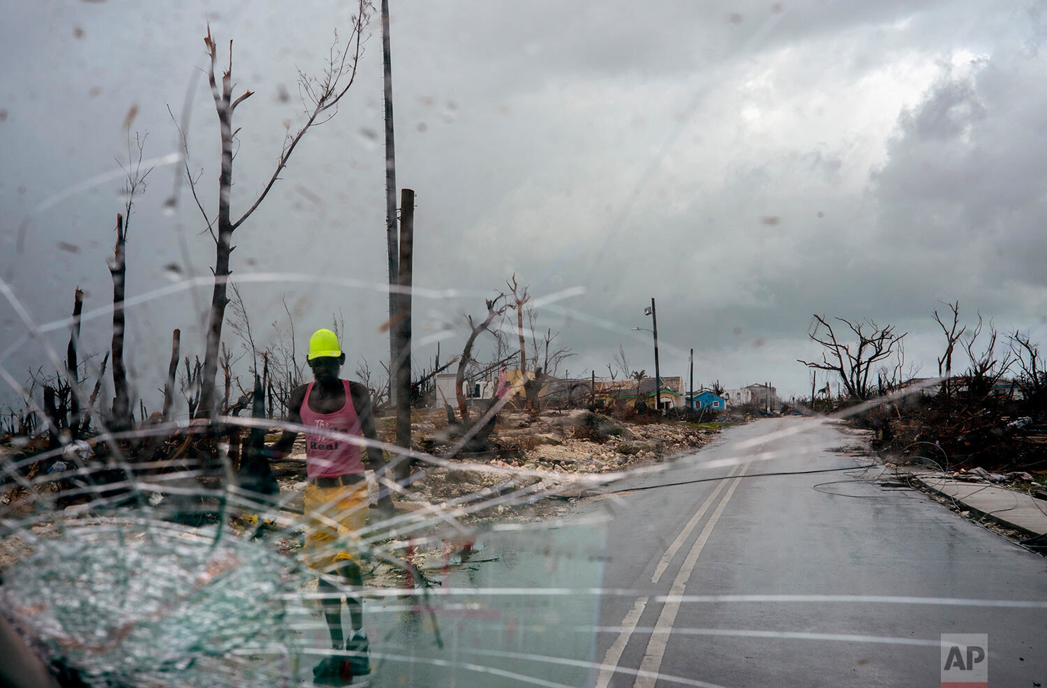 Trees destroyed by Hurricane Dorian line a road as a man walks by, in Abaco, Bahamas, Monday, Sept. 16, 2019. (AP Photo/Ramon Espinosa)