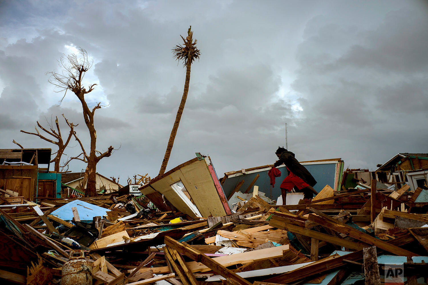 Vladimir Safford an immigrant from Haiti walks through the rubble next to his home in the aftermath of Hurricane Dorian in Abaco, Bahamas, Monday, Sept. 16, 2019. (AP Photo/Ramon Espinosa)