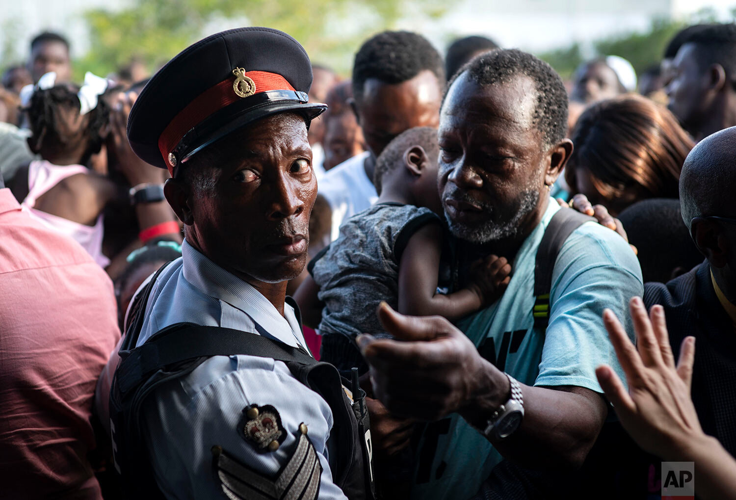 Haitian immigrants displaced from the island of Abaco because of Hurricane Dorian wait to get food from humanitarian organizations in Nassau, Bahamas, Sunday, Sept. 29, 2019.  (AP Photo / Ramon Espinosa)