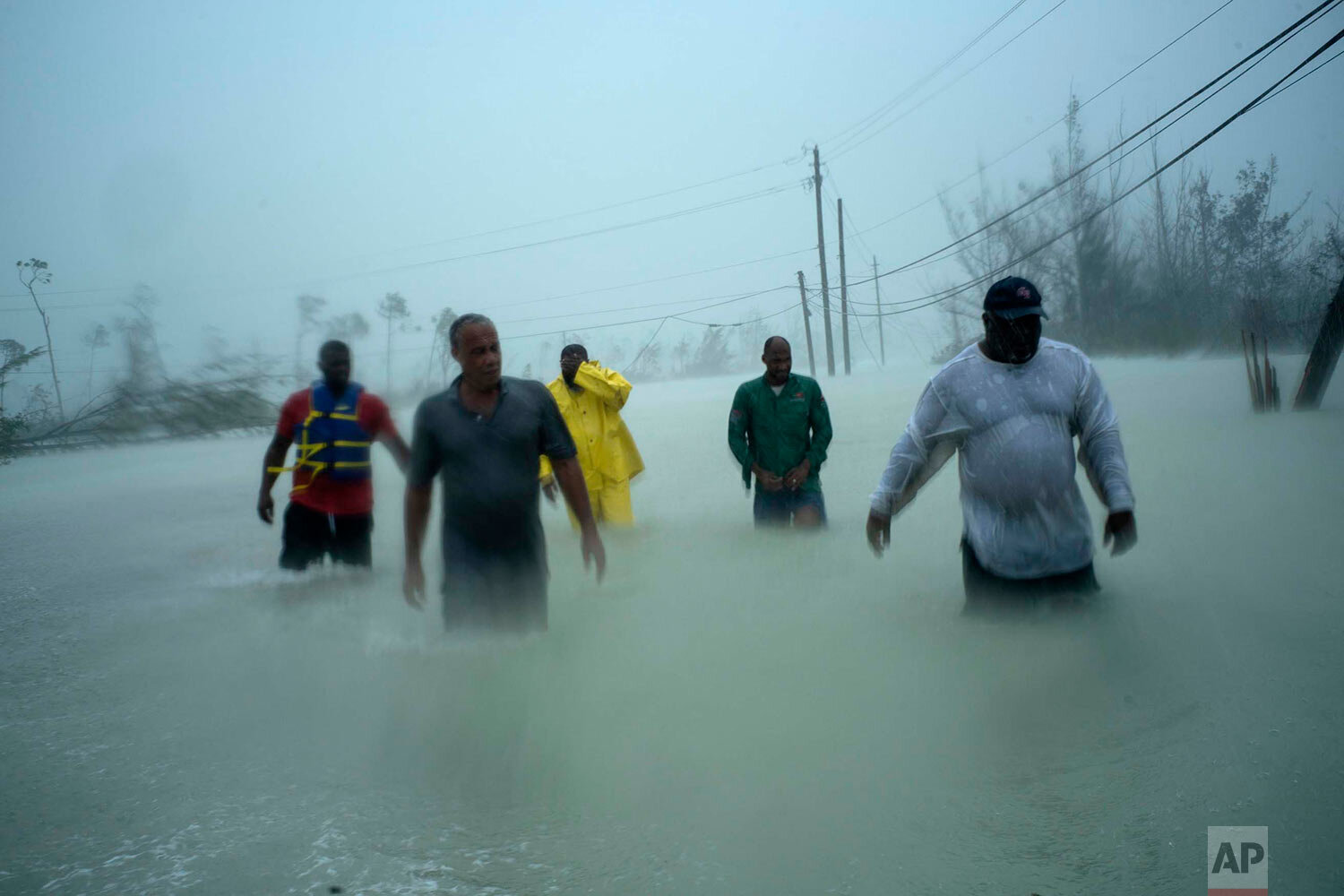 Volunteers walk under the wind and rain of Hurricane Dorian, on a flooded road after rescuing several families that arrived on small boats, near the Causarina bridge in Freeport, Grand Bahama, Bahamas, Tuesday, Sept. 3, 2019. (AP Photo/Ramon Espinosa)
