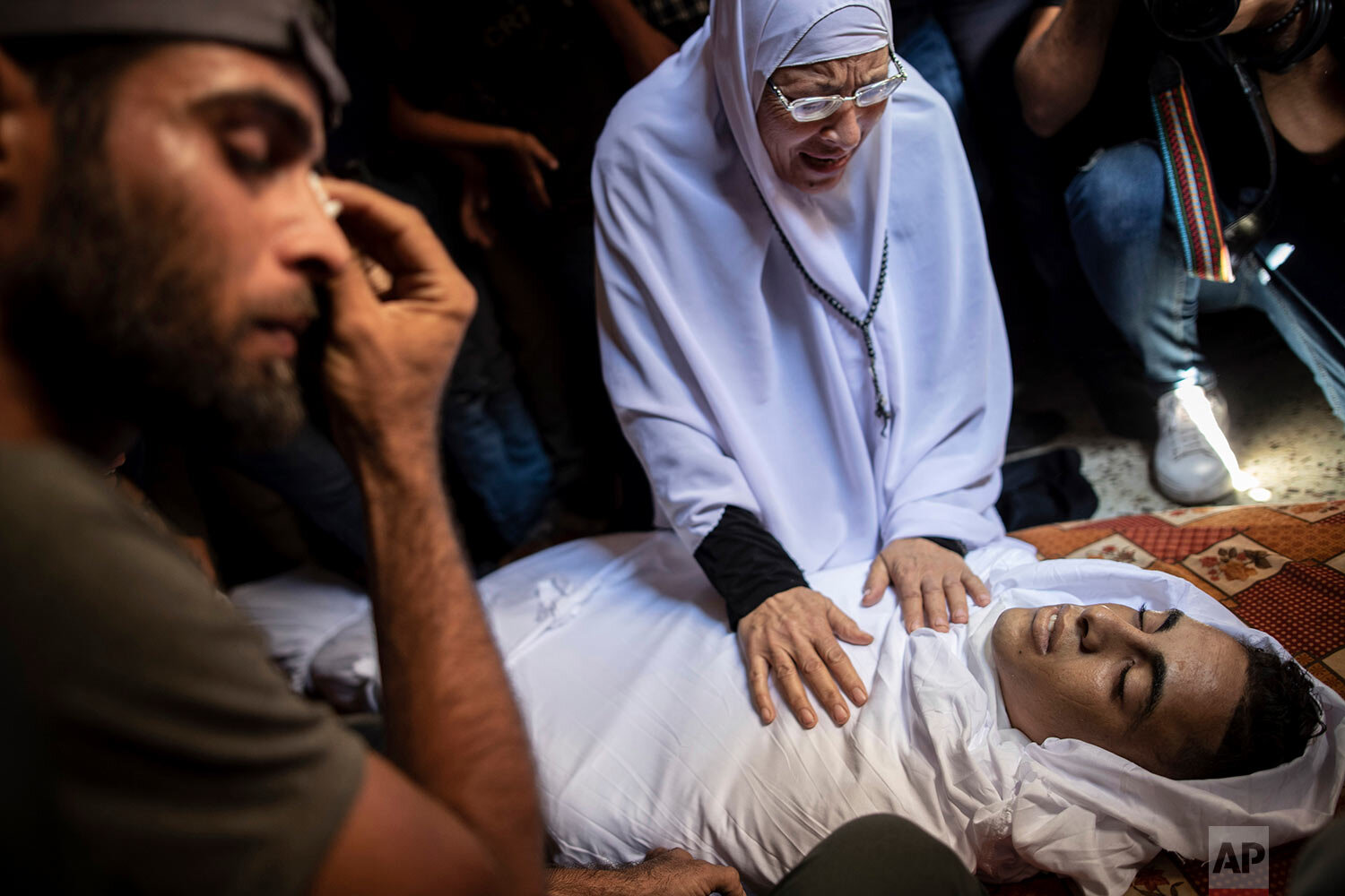 Relatives of Saher Othman, 20, mourn over his body in the family home during his funeral in Rafah refugee camp, southern Gaza Strip, Saturday, Sept. 28, 2019. Gaza's Health Ministry says Othman has been killed by Israeli gunfire during protests along Gaza-Israel border. (AP Photo/Khalil Hamra)